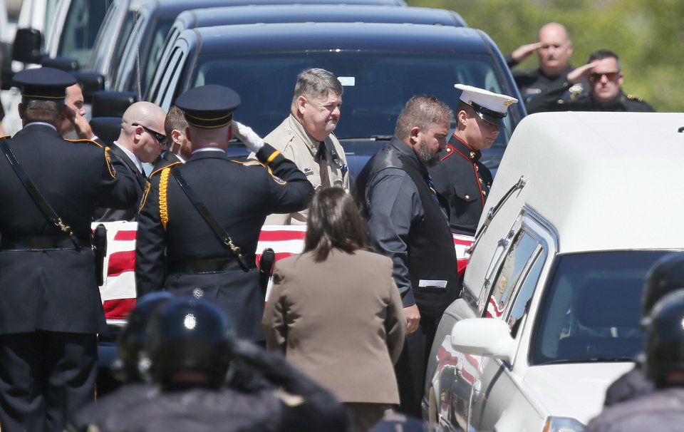 Photo - The flag-draped casket of Logan County Deputy David Wade is carried past an honor guard to the hearse following his funeral in Guthrie, Okla., Monday, April 24, 2017. Wade was shot and killed while serving an eviction notice near Mulhall, Okla,. on April 18. (AP Photo/Sue Ogrocki)