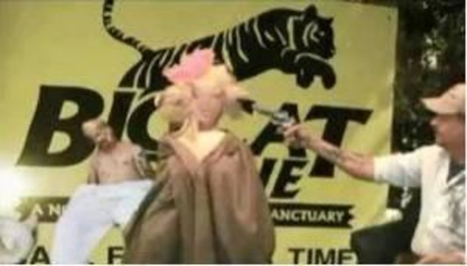 Photo -  In this screen grab from a 2014 video, Joe Exotic shoots an effigy of Carole Baskin, the alleged target of a murder-for-hire plot. Prosecutors put the video into evidence Thursday at a detention hearing.