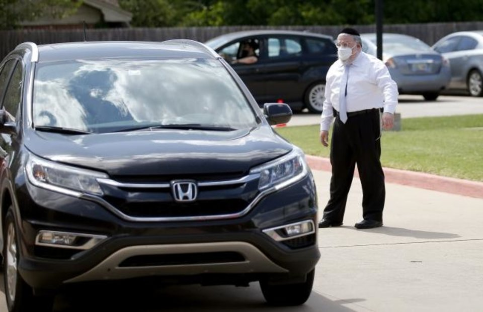 Photo -  Rabbi Ovadia Goldman directs traffic during a drive-thru mask distribution at Chabad Community Center for Jewish Life and Learning, where he is spiritual leader. [Sarah Phipps/The Oklahoman]