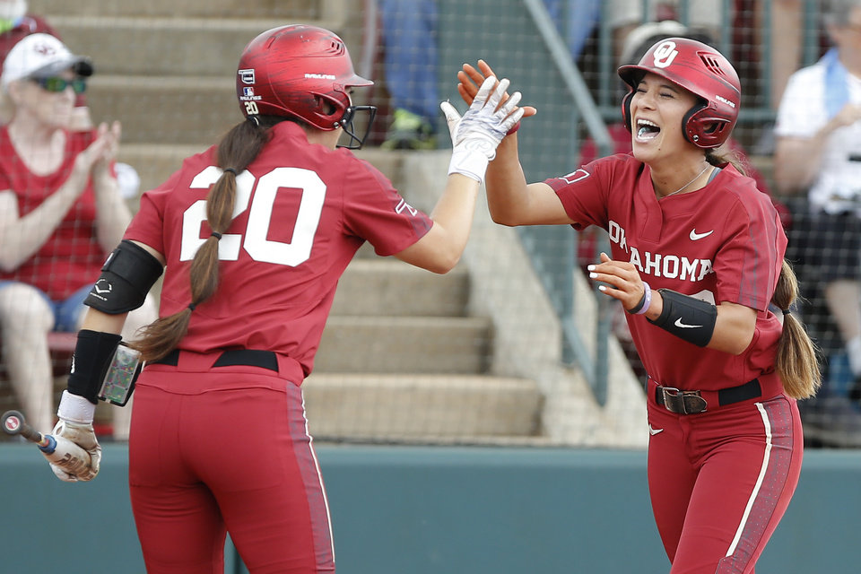 Photo - Oklahoma's Sydney Romero (2) celebrates with Caleigh Clifton (20) after scoring a run in the first inning of the second softball game in the Norman Super Regional between the University of Oklahoma (OU) and Northwestern in Norman, Okla., Saturday, May 25, 2019. Oklahoma won 8-0 to send them to the Women's College World Series. [Bryan Terry/The Oklahoman]