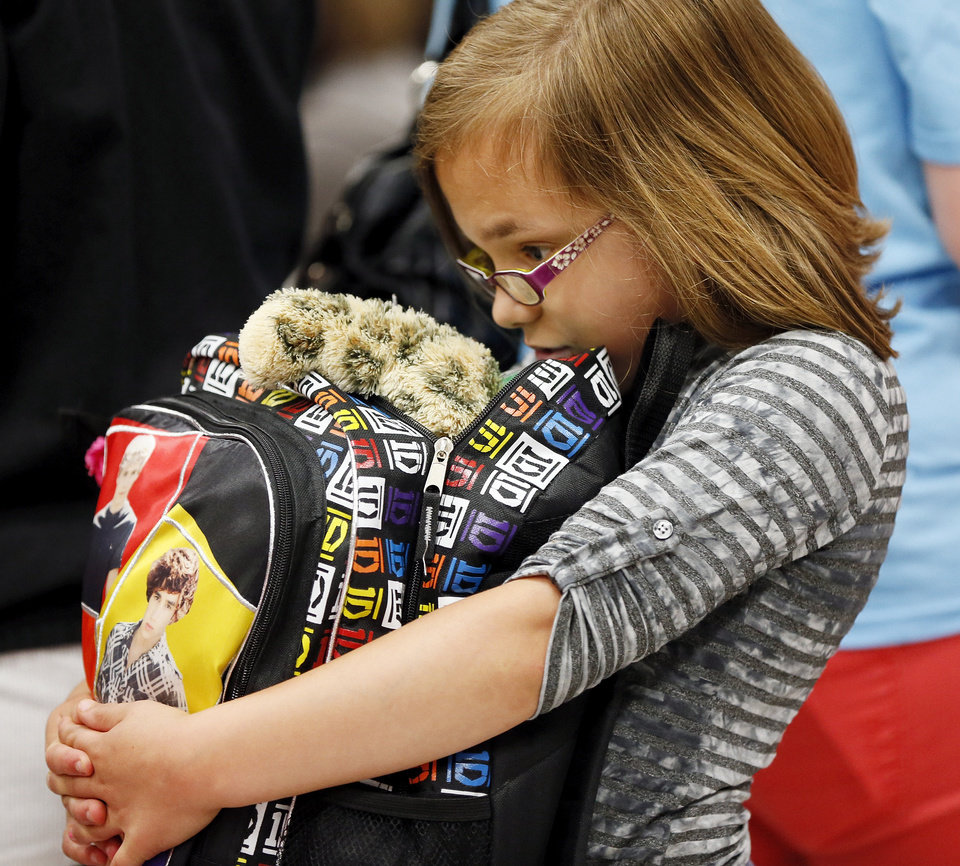 Photo - Third-grader Zandria Hannigan, 10, holds a backpack with donations she and other Plaza Towers students received during a meet and greet with teachers and students from Plaza Towers Elementary at Eastlake Elementary School in Oklahoma City, Thursday, May 23, 2013. Seven Plaza Towers students died when a tornado destroyed the school in Moore, Okla., on Monday. Hannigan and her 2 siblings that attend Plaza Towers came home early from school on Monday because Hannigan was having allergies. Photo by Nate Billings, The Oklahoman