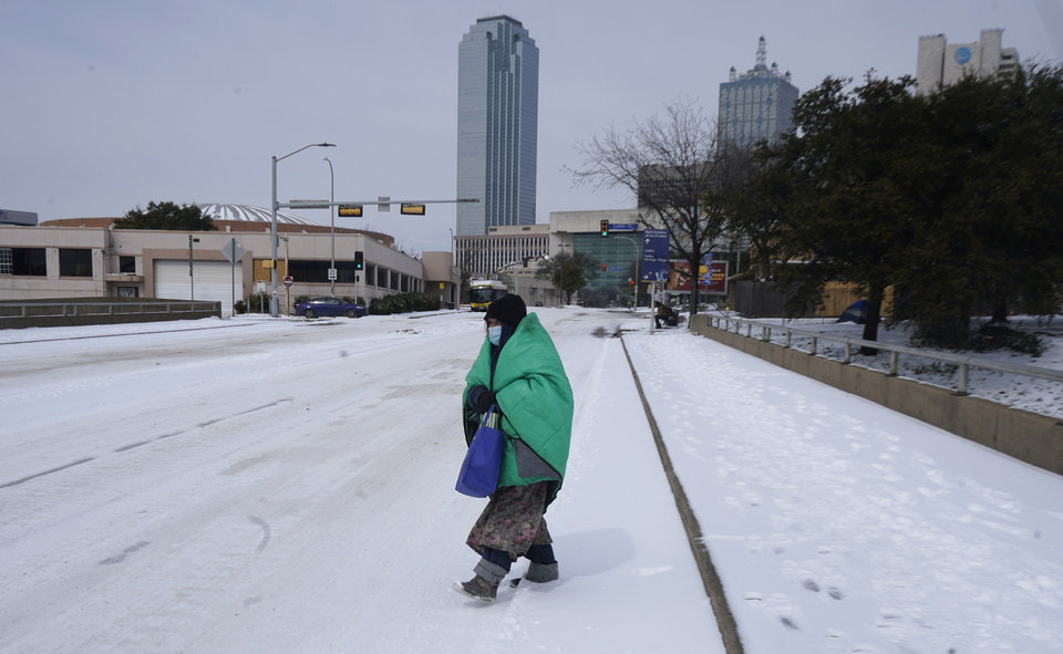 Photo -  FILE - In this Feb. 16, 2021, file photo, a woman wrapped in a blanket crosses the street near downtown Dallas. As temperatures plunged and snow and ice whipped the state, much of Texas' power grid collapsed, followed by its water systems. Tens of millions huddled in frigid homes that slowly grew colder or fled for safety. (AP Photo/LM Otero, File)