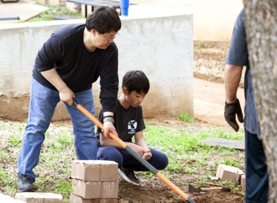 Photo -  John and Joshua Yim assist with landscape work at Central Middle School. [PHOTO PROVIDED]