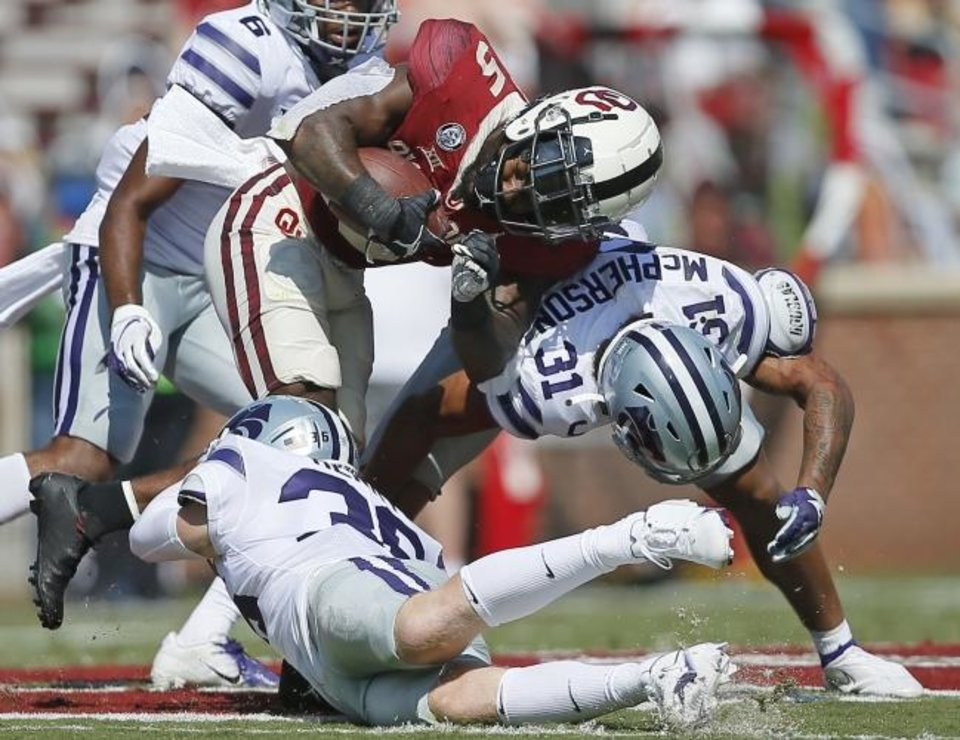 Photo -  Oklahoma's T.J. Pledger, middle, gets past Kansas State's Hunter Henry, bottom, and Jahron McPherson, right, earlier this season. [Bryan Terry/The Oklahoman]