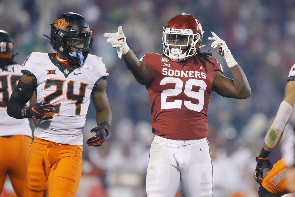 Photo - Oklahoma's Rhamondre Stevenson (29) celebrates beside Oklahoma State's Jarrick Bernard-Converse (24) during a Bedlam college football game between the University of Oklahoma Sooners (OU) and the Oklahoma State Cowboys (OSU) at Gaylord Family-Oklahoma Memorial Stadium in Norman, Okla., Saturday, Nov. 21, 2020. Oklahoma won 41-13. [Bryan Terry/The Oklahoman]