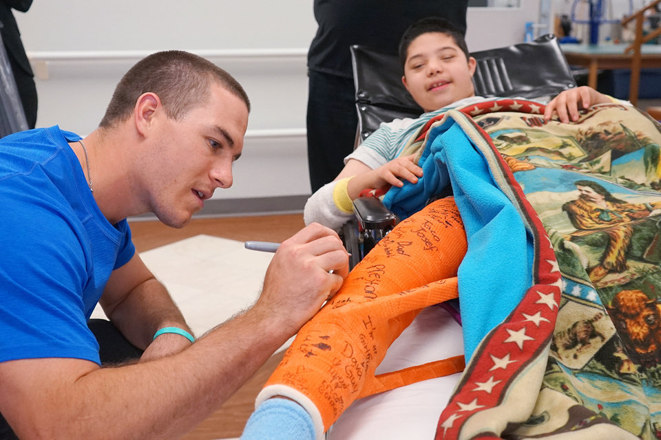 Photo -  Miami Marlins catcher and Carl Albert High alum J.T. Realmuto signs the cast of Simon Foss at The Children's Center Rehabilitation Hospital. Realmuto has made fans out of the folks at the Bethany facility with his regular visits and his strong connection to the patients. [PHOTO COURTESY OF THE CHILDREN'S CENTER]