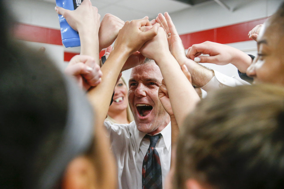 Photo - Mustang head coach Kevin Korstjens yells in excitement after his team sprayed water on him after their OSSAA quarterfinal win over Putnam City West High School at Memorial High School on Thursday, March 7, 2019. IAN MAULE/Tulsa World