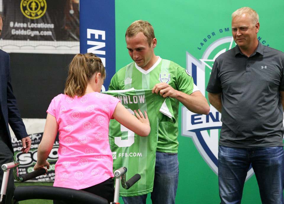 Photo - Emma receives her team jersey from Kyle Hyland, her Energy FC Sidekicks buddy. Photo courtesy of Prodigal LLC.