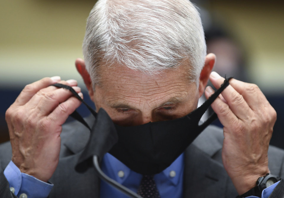 Photo -  Director of the National Institute of Allergy and Infectious Diseases Dr. Anthony Fauci takes off his face mask before testifying before a House Committee on Energy and Commerce on the Trump administration's response to the COVID-19 pandemic on Capitol Hill in Washington on Tuesday, June 23, 2020. (Kevin Dietsch/Pool via AP)