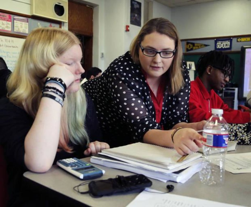 Photo -  Math instructor Jennifer Burris works with student Rebekah Rambo at Harding Fine Arts Academy. Students were calculating the surface area of various three-dimensional shapes as they used recycled objects to build a Tin Man. [Photo by Paul Hellstern, The Oklahoman]