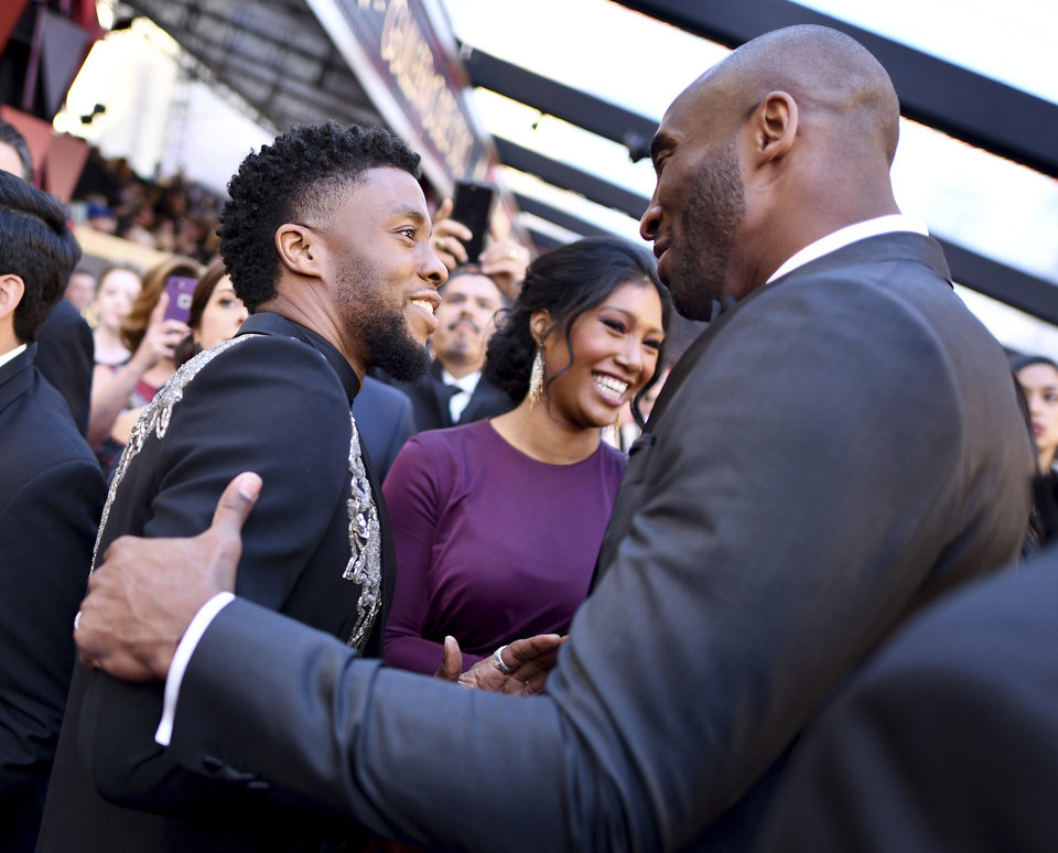 Photo - Chadwick Boseman, left, greets Kobe Bryant at the Oscars on Sunday, March 4, 2018, at the Dolby Theatre in Los Angeles. (Photo by Charles Sykes/Invision/AP)