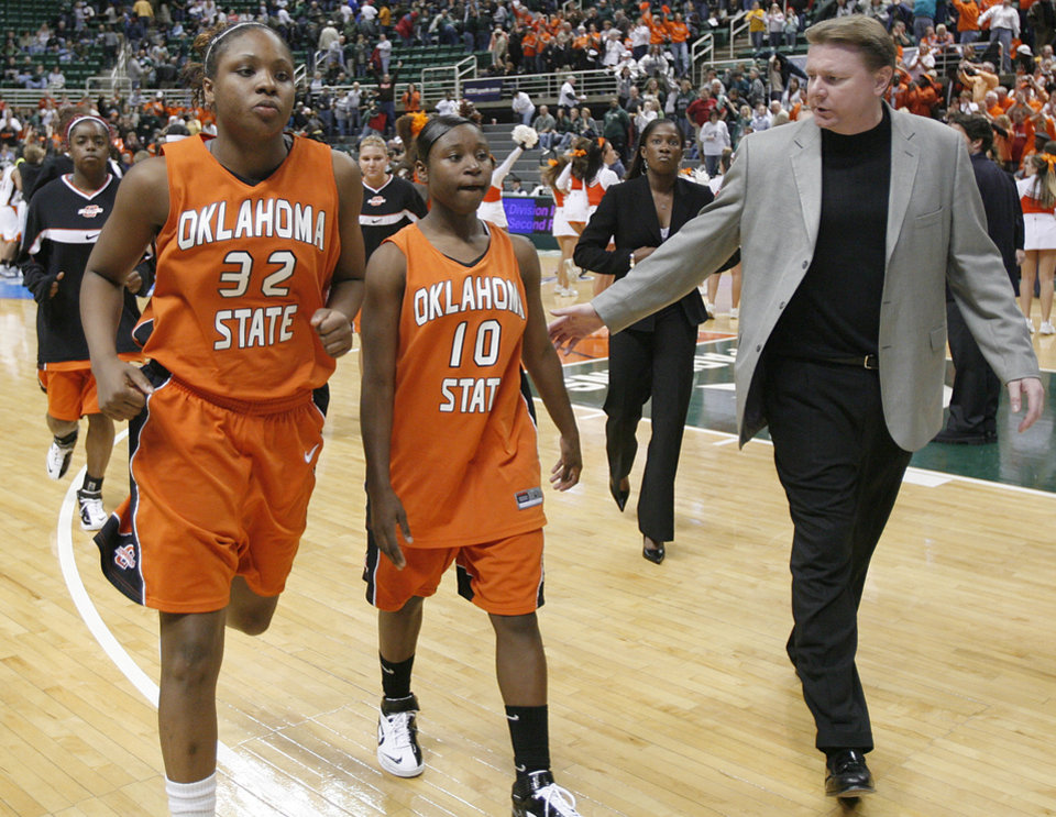 Photo - Oklahoma State Universitiy head coach Kurt Budke walks off the court with Shaunte Smith (32) and Andrea Riley (10) after the loss to Bowling Green in the first round game of the women's NCAA Tournament in the Jack Breslin Arena at Michigan State University on Sunday, March 18, 2007, in East Lansing, Mich.   staff photo by CHRIS LANDSBERGER