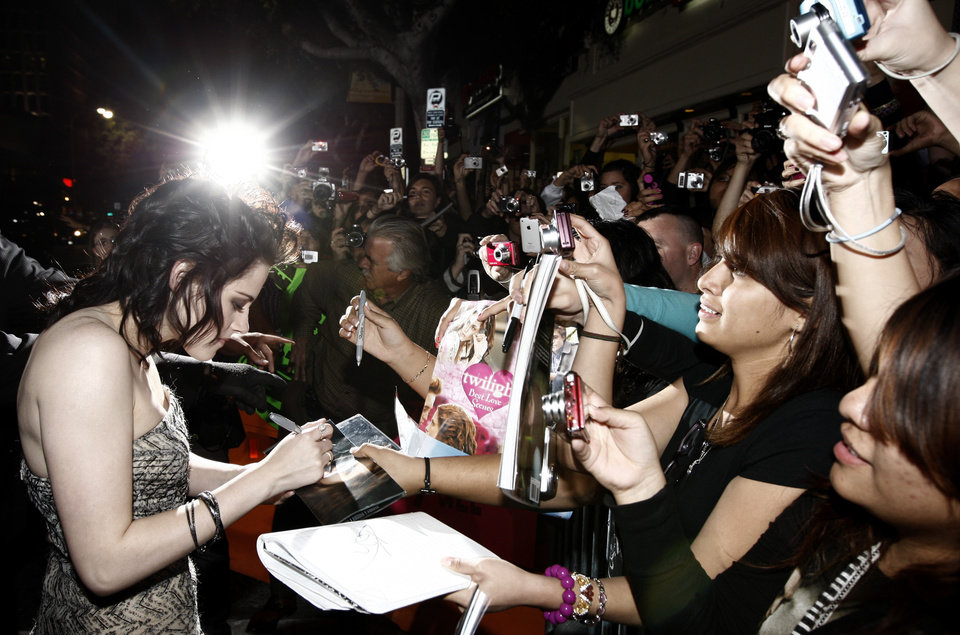 Photo - Actress Kristen Stewart signs autographs as she arrives at The Twilight Saga: New Moon premiere in Westwood, Calif. Monday, Nov. 16, 2009.  (AP Photo/Matt Sayles) ORG XMIT: CAGS143
