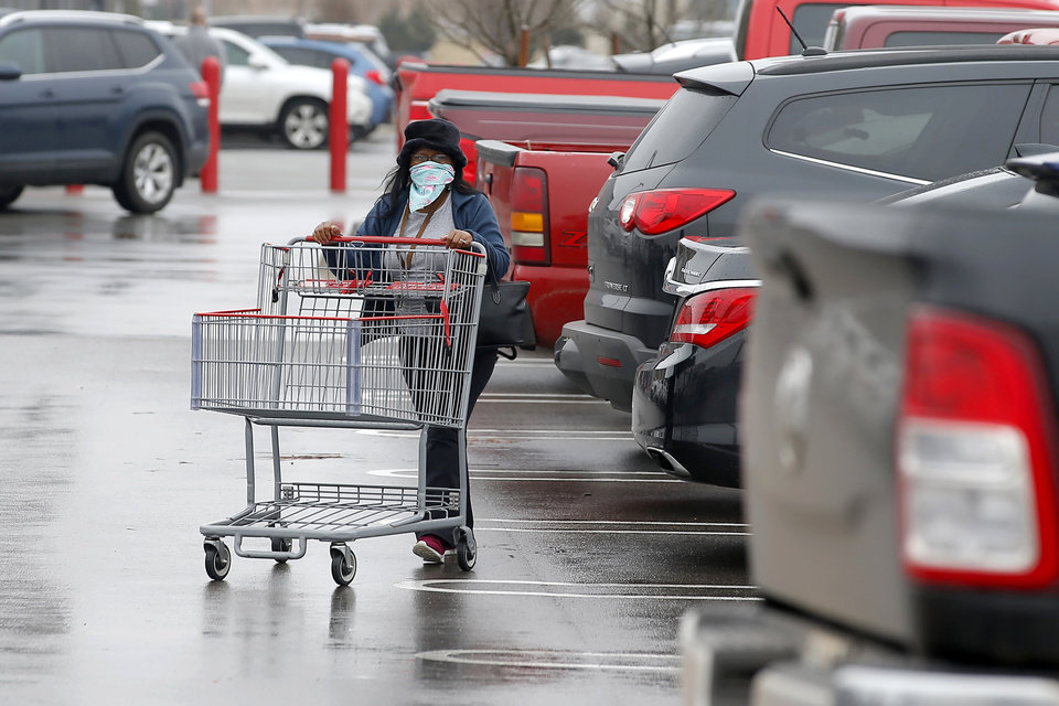 Photo - A shopper covers her face as she returns a shopping cart at Costco in Oklahoma City, Tuesday, March 17, 2020. [Bryan Terry/The Oklahoman]