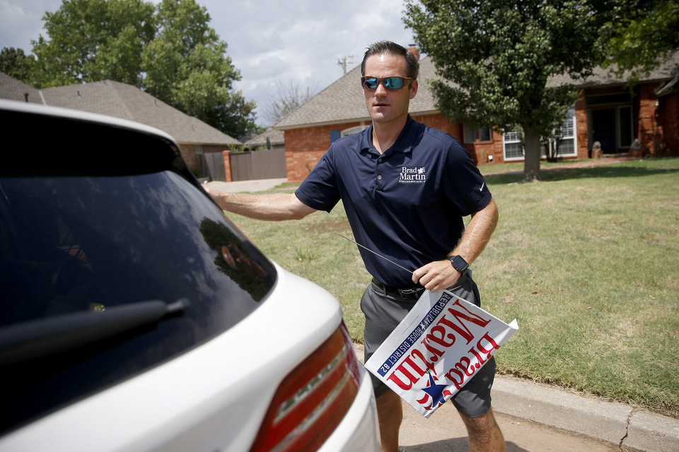 Photo -  Brad Martin, who is in the House District 82 Republican runoff, takes a sign out of his car Aug. 7 before placing it as he campaigns in Oklahoma City. [Photo by Bryan Terry, The Oklahoman]