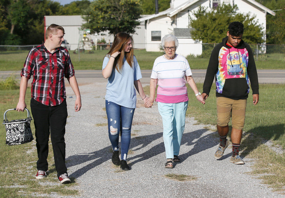 Photo - Volunteer Neva Kitsmiller, second from right, is walked home by students, from left,  Chance Taylor, 18, of Duncan, Raegan Wylie, 15, of Comanche, and Adam Stedman, 17, of Comanche, after Kitsmiller taught crochet at FAME Academy, an alternative school in Comanche Public Schools, in Meridian, Okla., Wednesday, Oct. 3, 2018. Photo by Nate Billings, The Oklahoman