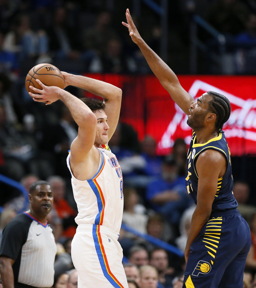 Photo - Oklahoma City's Danilo Gallinari (8) looks to pass around Indiana's T.J. Warren (1) in the third quarter during an NBA basketball game between the Indiana Pacers and the Oklahoma City Thunder at Chesapeake Energy Arena in Oklahoma City, Wednesday, Dec. 4, 2019. Indiana won 107-100. [Nate Billings/The Oklahoman]