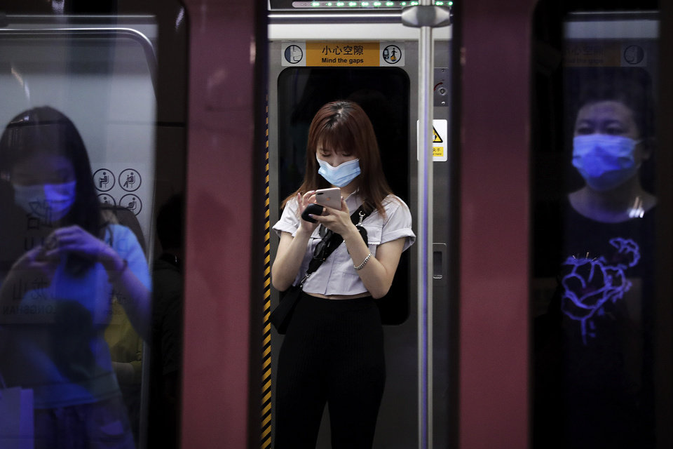 Photo -  Commuters wearing face masks to protect against the new coronavirus ride in a subway train in Beijing, Wednesday, July 29, 2020. China reported more than 100 new cases of COVID-19 on Wednesday as the country continues to battle an outbreak in Xinjiang. (AP Photo/Andy Wong)