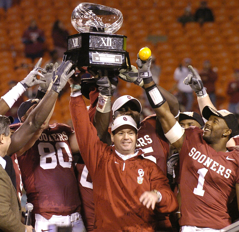 Photo - KANSAS, MO, SATURDAY, DECEMBER 4, 2004. UNIVERSITY OF OKLAHOMA (OU) SOONERS VS COLORADO BIG 12 (TWELVE) CHAMPIONSHIP COLLEGE FOOTBALL AT ARROWHEAD STADIUM IN KANSAS, MO.    CELEBRATE, TROPHY: Oklahoma Sooners head coach Bob Stoops celebrates the Big 12 Championship with his team after defeating  Colorado Saturday night in Kansas City. By Ty Russell/The Oklahoman.