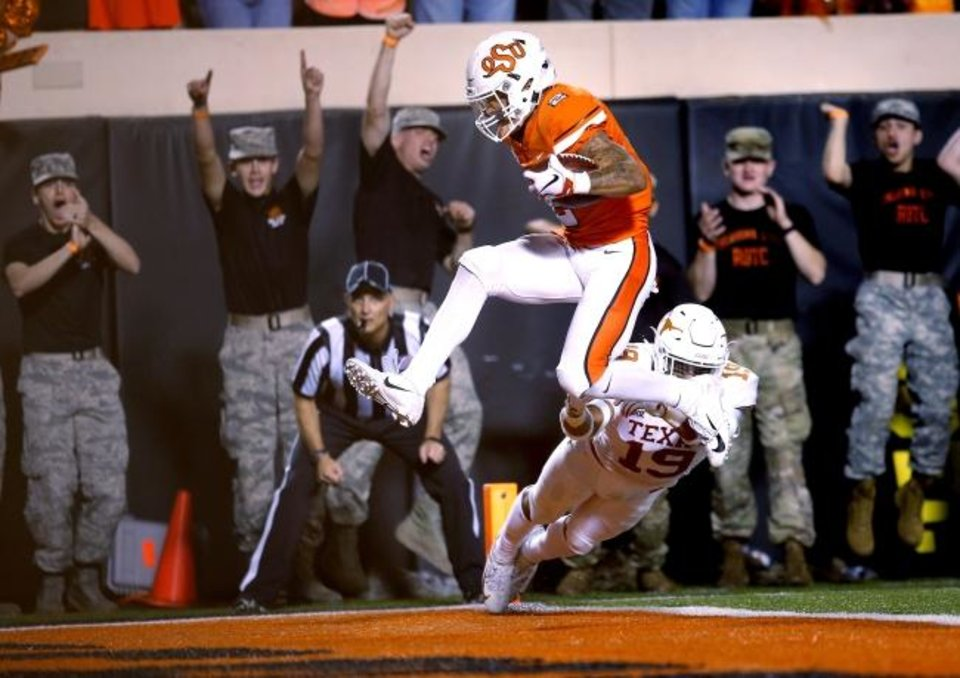 Photo -  Oklahoma State's Tylan Wallace scores past Texas's Brandon Jones last season. [Sarah Phipps/The Oklahoman]