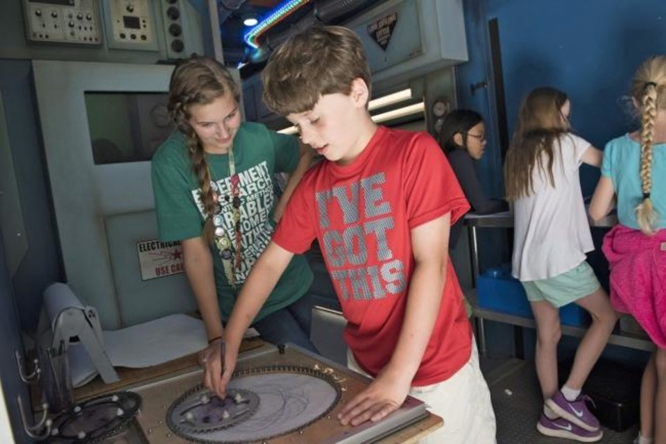 Photo -  A teen apprentice, left, watches as a Science Museum Oklahoma camper operates an exhibit. [PHOTO PROVIDED]
