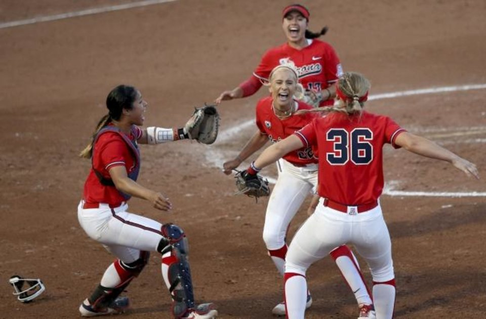 Photo -  Arizona players rush the circle and starter Alyssa Denham, center, after the final out in Game 2 of the Wildcats' super regional against Mississippi on Saturday in Tucson, Ariz. [Kelly Presnell/Arizona Daily Star via AP]