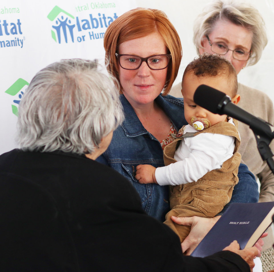 Photo - Brittani Githiri holds her son, Piaget, 1, while receiving a Bible from Nancy Riddell, Central Oklahoma Habitat Board of Directors, as Ann Felton Gilliland looks on. Habitat for Humanity's 1,000th home, Monday, March 9, 2020.  [Photo by Doug Hoke/The Oklahoman]