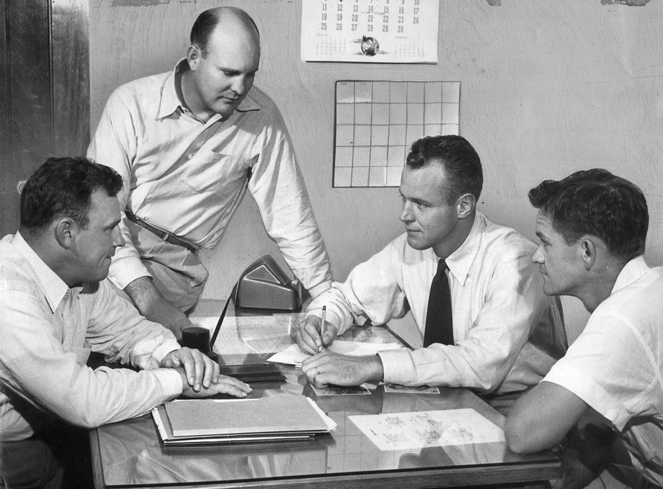 Photo - Bud Wilkinson (second from right) chats with his 1949 staff: Gomer Jones (left), Pop Ivy (standing) and Bill Jennings. (Oklahoman archive photo)