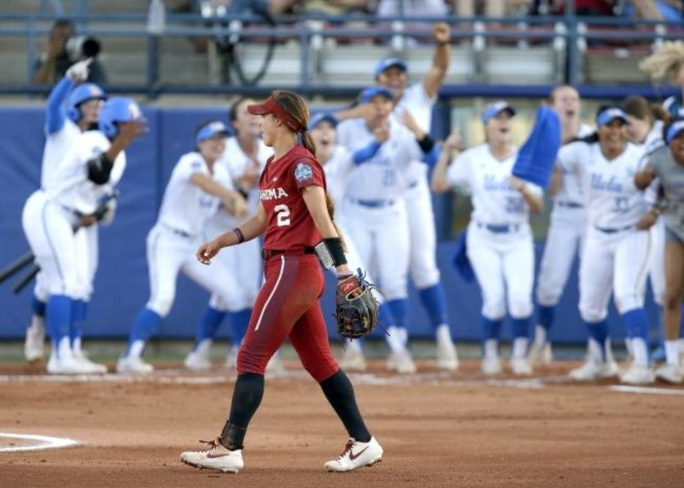 Photo -  UCLA players celebrate behind Oklahoma's Sydney Romero (2) after their second home run in the first inning of the second NCAA softball game in the championship series of the Women's College World Series between Oklahoma and UCLA at USA Softball Hall of Fame Stadium in Oklahoma City, Tuesday, June 4, 2019. [Bryan Terry/The Oklahoman]