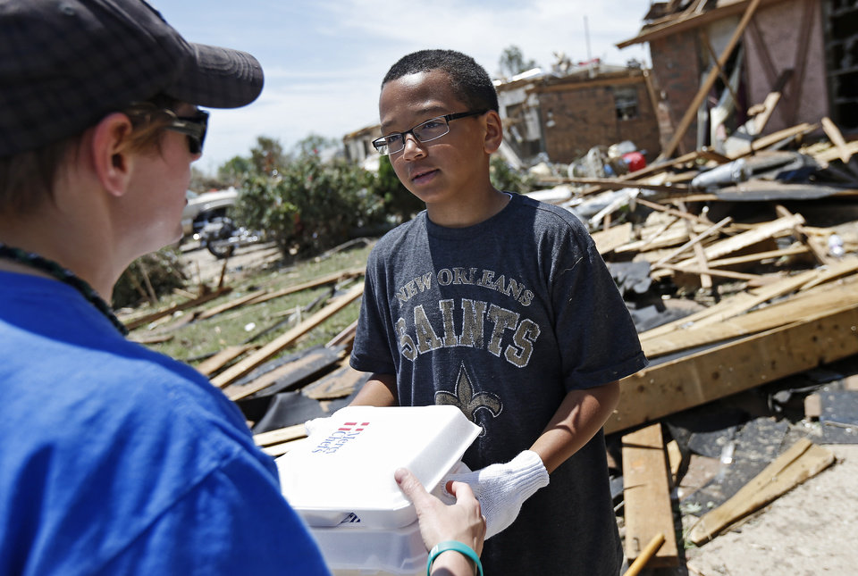 Photo - Southgate Baptist Church volunteer  Angie Sullivan pass out a Mercy Chefs meal to tornado victim Darius Waters, 11, in Moore, Okla., Wednesday, May 22, 2013. A tornado damaged the area on Monday, May 20, 2013. Photo by Bryan Terry, The Oklahoman