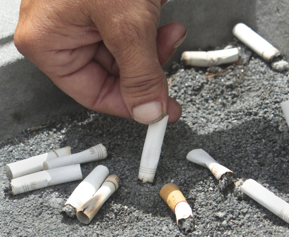 Photo - A smoker snuffs out a cigarette In this June 22, 2012, file photo. (AP Photo/Rich Pedroncelli)