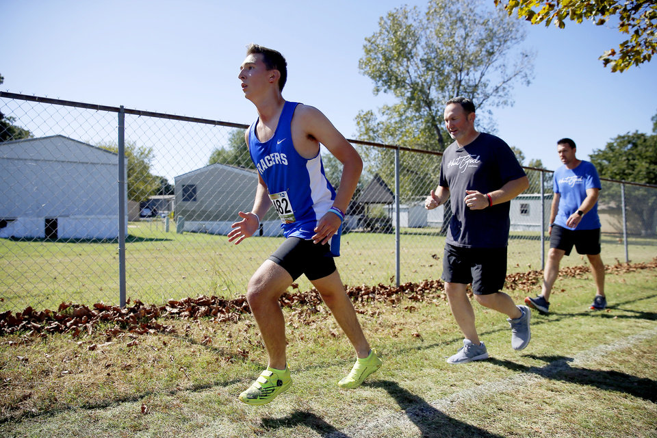 Photo - Newcastle runner Caleb Freeman, who was injured in a 2017 car crash, is followed by his father Jeremy Freeman, center, and Shawn Wright as he runs a cross country race at Carl Albert in Midwest City, Okla., Tuesday, Oct. 8, 2019.This was Caleb Freeman's first cross country race since getting injured in a 2017 car wreck. [Bryan Terry/The Oklahoman]