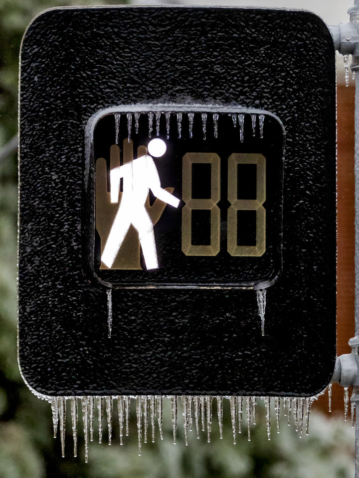 Photo - Ice covers a crosswalk sign in Oklahoma City, Okla. on Tuesday, Oct. 27, 2020, after a winter blast covered the state with ice. [Chris Landsberger/The Oklahoman]