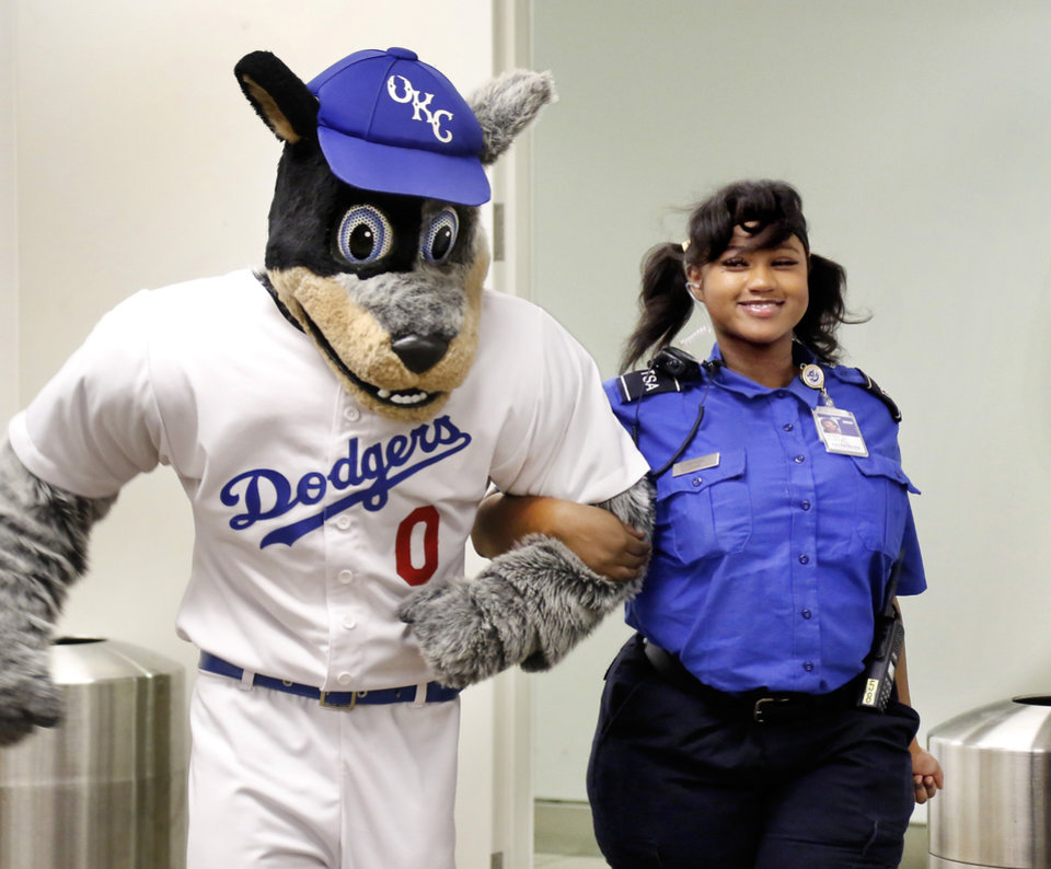 Photo -  Brix, one of two Oklahoma City Dodgers mascots, greets Arora Watkins on Wednesday at Will Rogers World Airport. [Photo by Jim Beckel, The Oklahoman]