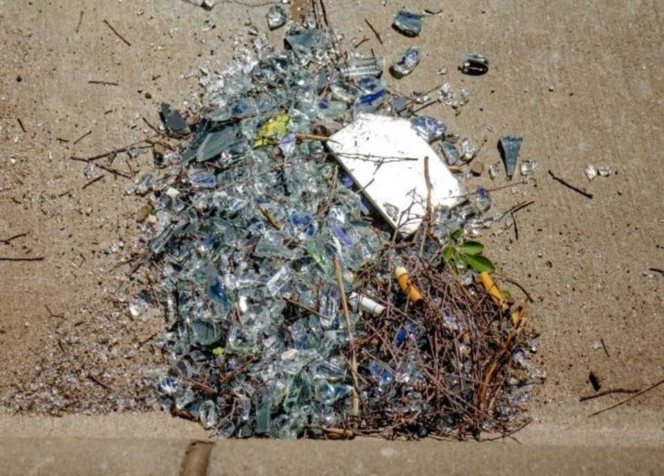 Photo -  A pile of glass shards and debris are gathered in a downtown street after window washers' equipment broke loose Wednesday near the top of the Devon Tower.  [Chris Landsberger/The Oklahoman]