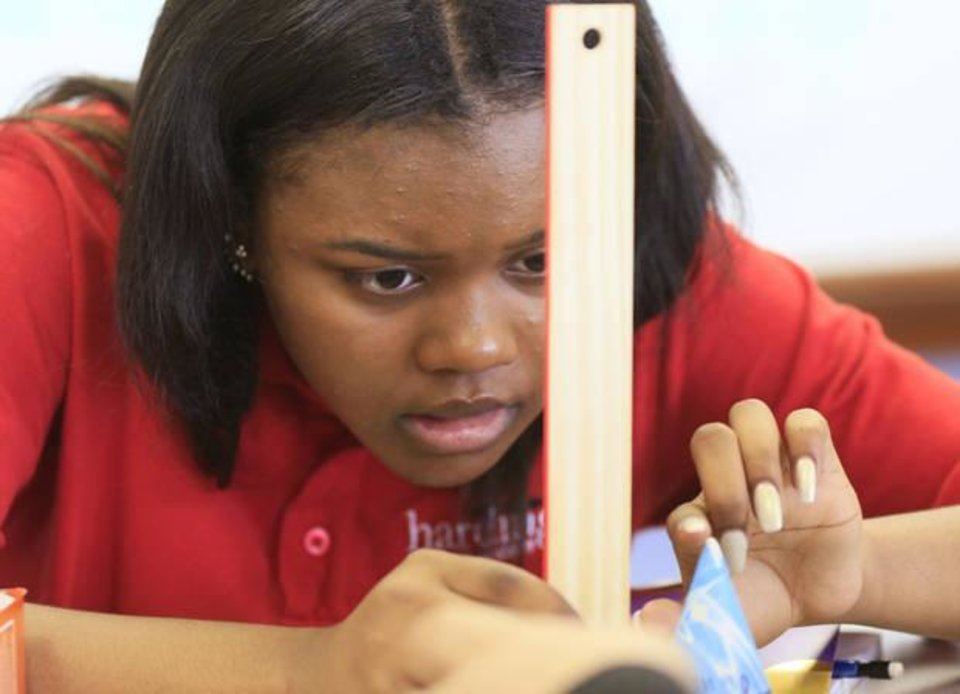 Photo -  Deja West measures the height of a cone in Jennifer Burris' geometry class at Harding Fine Arts Academy. [Photo by Paul Hellstern, The Oklahoman]