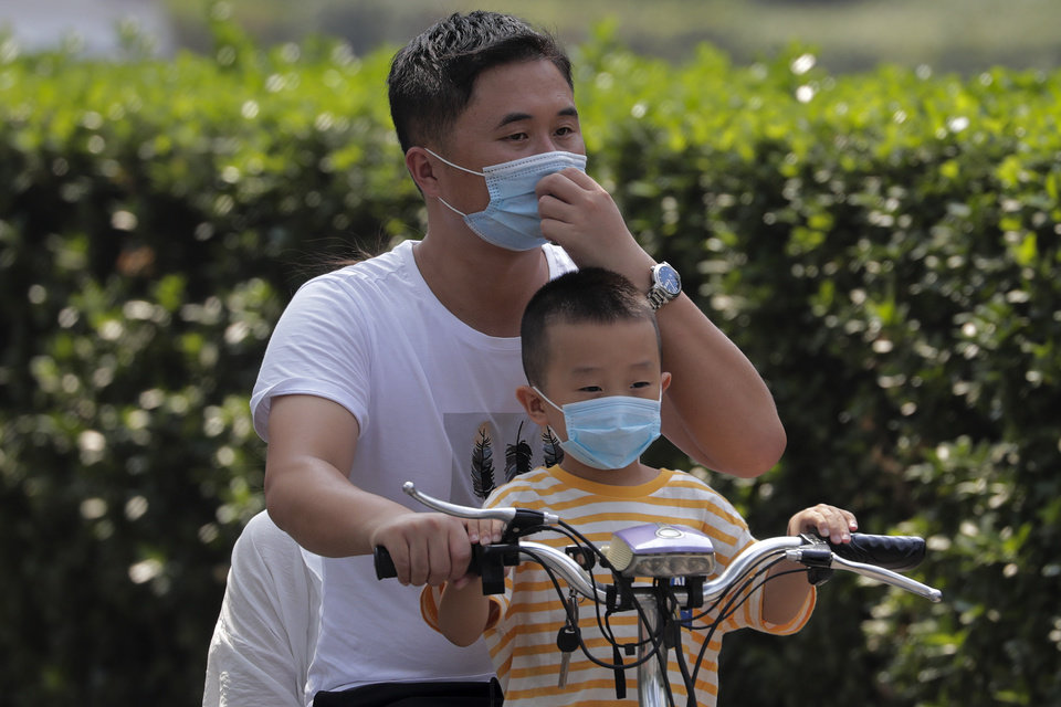 Photo -  A man and a child wearing face masks to help curb the spread of the coronavirus ride on an electric-powered scooter past the Xinfadi wholesale food market district, Sunday in Beijing. [Andy Wong/the associated press]