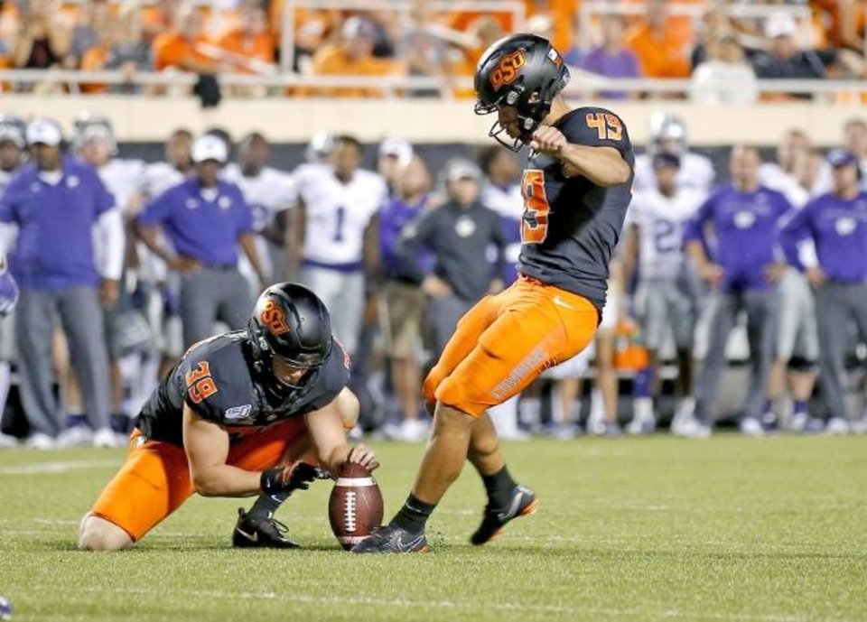 Photo -  Oklahoma State's Matt Ammendola, right, kicks a field goal as Jake McClure holds during the fourth quarter of Saturday's 26-13 win over Kansas State Saturday. [Sarah Phipps/The Oklahoman]