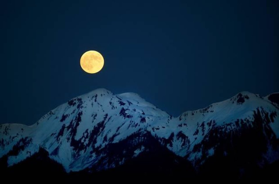 Photo - A full moon rises over a mountain range in southeast Alaska on June 4, 2012. Photo by Sarah Phipps, The Oklahoman