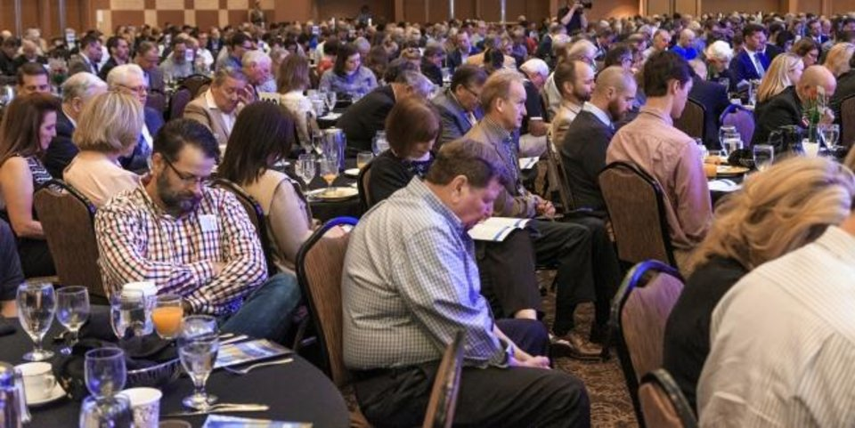 Photo -  Attendees bow their heads in prayer during the 2018 CBMC Metro Prayer Breakfast at the Cox Convention Center in Oklahoma City. [Chris Landsberger/The Oklahoman]