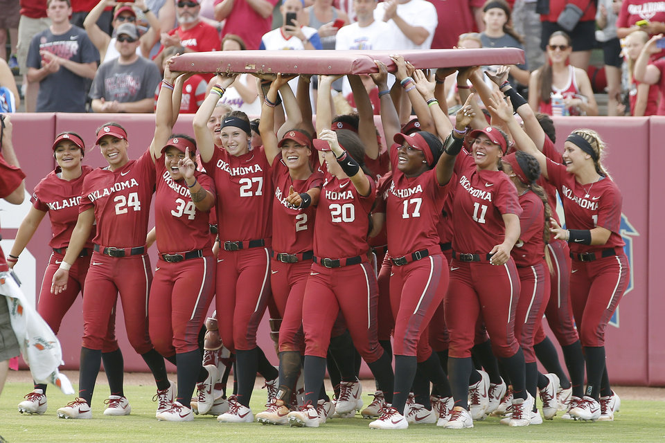 Photo - Oklahoma players carry a piece of the outfield wall after winning the second game of the NCAA softball tournament in the Norman Super Regional between the University of Oklahoma (OU) and Northwestern in Norman, Okla., Saturday, May 25, 2019. Oklahoma won 8-0 to send them to the Women's College World Series.[Bryan Terry/The Oklahoman]