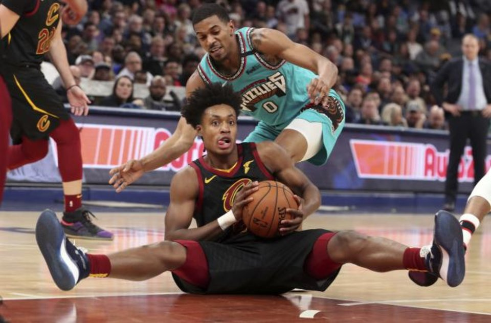 Photo -  Memphis Grizzlies guard De Anthony Melton (0) defends against Cleveland Cavaliers guard Collin Sexton during Friday night's game. Memphis defeated Cleveland 113-109. [AP Photo/Karen Pulfer Focht]