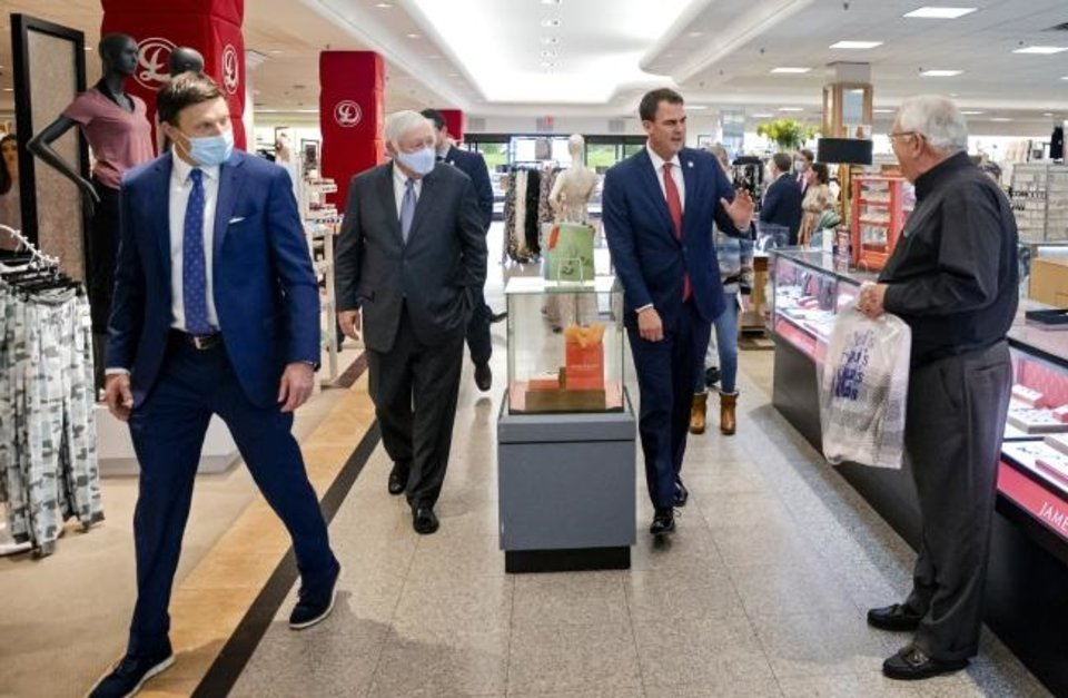 Photo -  Gov. Kevin Stitt waves to a customer as he talks with Dillard´s CEO Bill Dillard II and Vice President Bill Dillard III, left, as Stitt tours the Oklahoma City Dillard´s at Penn Square Mall in this photo taken during the reopening of the mall. [CHRIS LANDSBERGER/THE OKLAHOMAN]