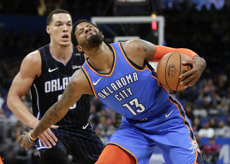 Photo - Oklahoma City Thunder's Paul George (13) grimaces after he is fouled by Orlando Magic's Aaron Gordon, left, during the first half of an NBA basketball game, Tuesday, Jan. 29, 2019, in Orlando, Fla. (AP Photo/John Raoux)