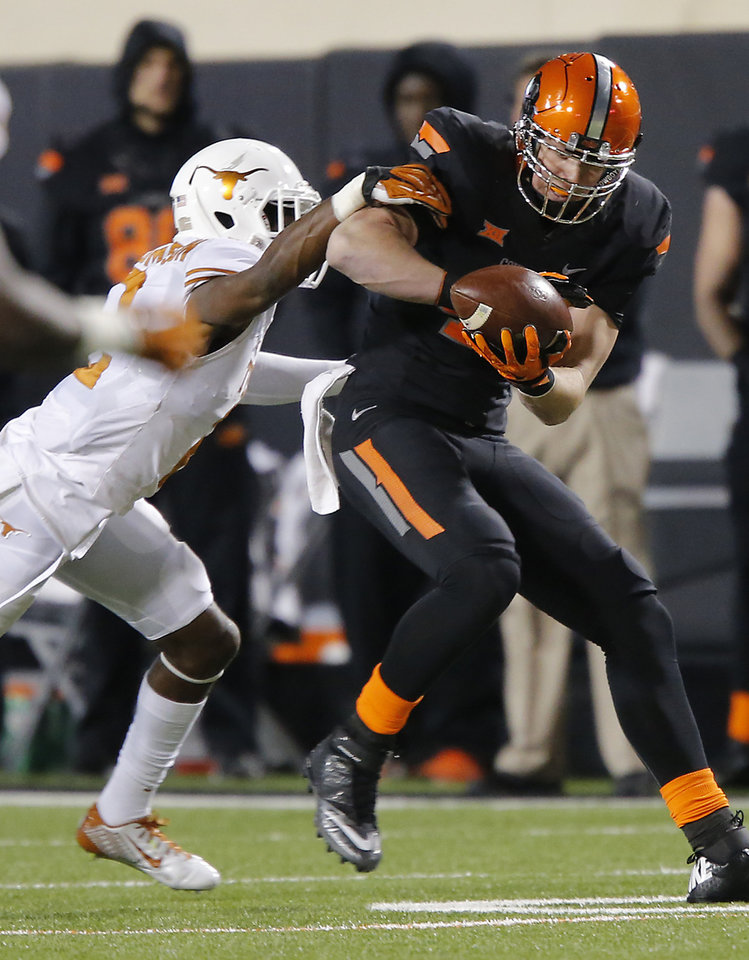 Photo - Oklahoma State's Blake Jarwin (47) makes a catch in front of Texas' Mykkele Thompson (2) during the college football game between the Oklahoma State University Cowboys (OSU) the University of Texas Longhorns (UT) at Boone Pickens Staduim in Stillwater, Okla. on Saturday, Nov. 15, 2014.  Photo by Chris Landsberger, The Oklahoman