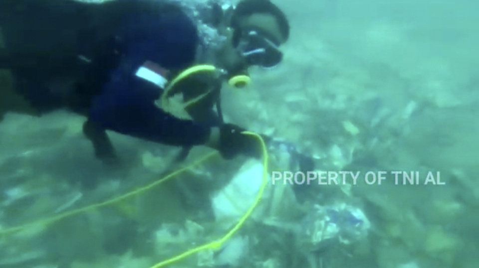Photo -  A diver is seen recovering debris strewn on the sea floor in Java Sea, where Sriwijaya Air passenger jet crashed, in Indonesia. [Indonesian Navy via The Associated Press]