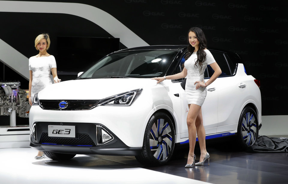Photo - Models pose with the GAC Motors GE3 electric car at the North American International Auto Show in Detroit, Monday, Jan. 9, 2017. (AP Photo/Paul Sancya)