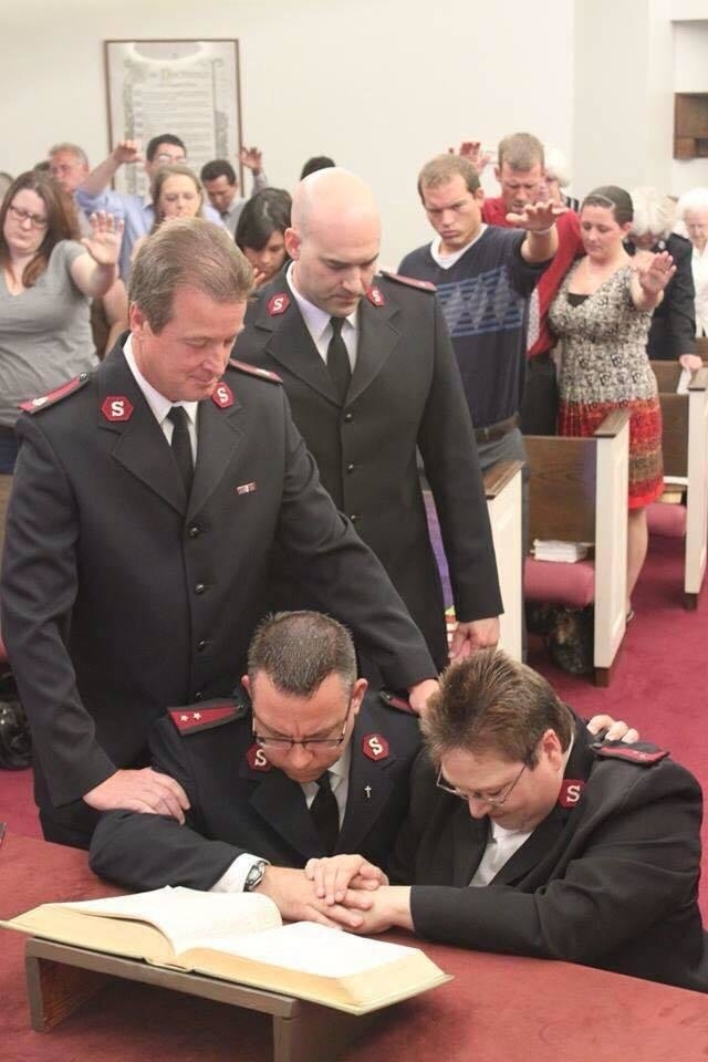 Photo - Salvation Army leaders lay hands on Salvation Army Majors Carlyle and Charlotte Gargis during a recent service. [Photo provided]
