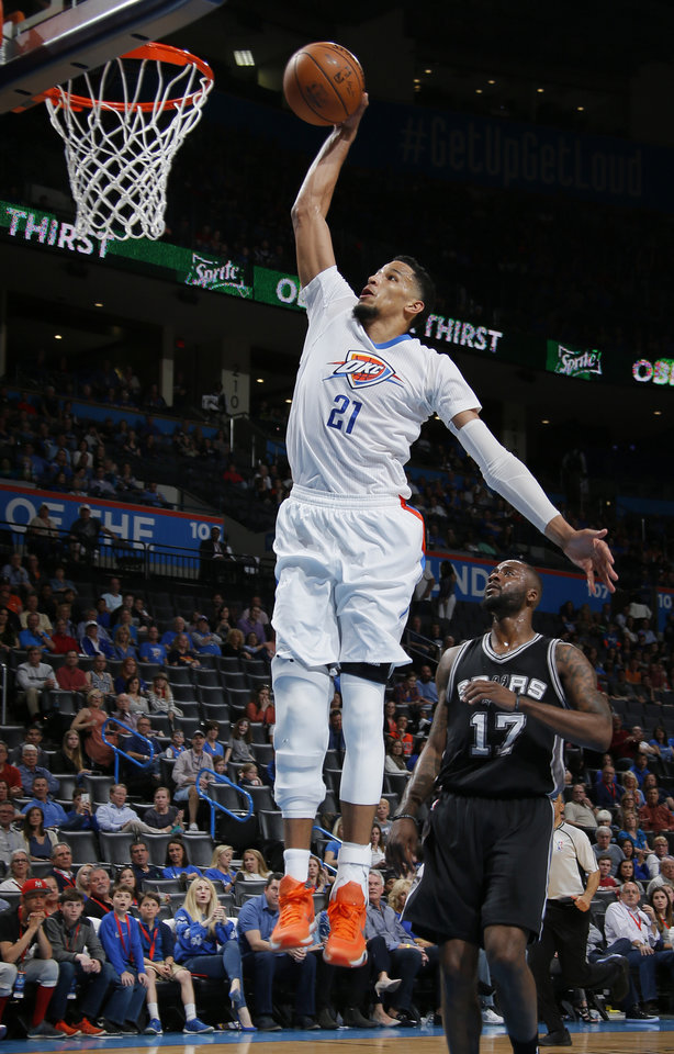 Photo - Oklahoma City's Andre Roberson (21) goes up for a dunk in front of San Antonio's Jonathon Simmons (17) during an NBA basketball game between the Oklahoma City Thunder and the San Antonio Spurs at Chesapeake Energy Arena in Oklahoma City, Saturday, March 26, 2016. Oklahoma City won 11-92. Photo by Bryan Terry, The Oklahoman