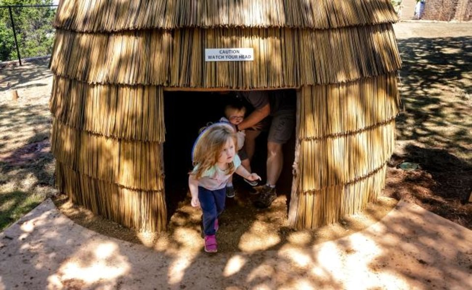 Photo -  Chole Turk, 3, and her brother Aiden check out the intertribal Native village, which is part of the newly opened Liichokoshkomo', a $15 million outdoor attraction at the National Cowboy & Western Heritage Museum.  [Chris Landsberger/The Oklahoman]